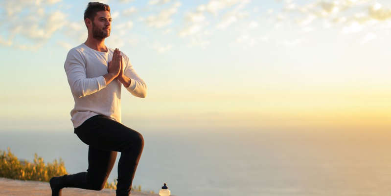 a man standing on a beach: Yoga is a great way to reduce stress, improve sleep, and even lose weight. Here's what an expert says you should know about trying yoga for weight loss.