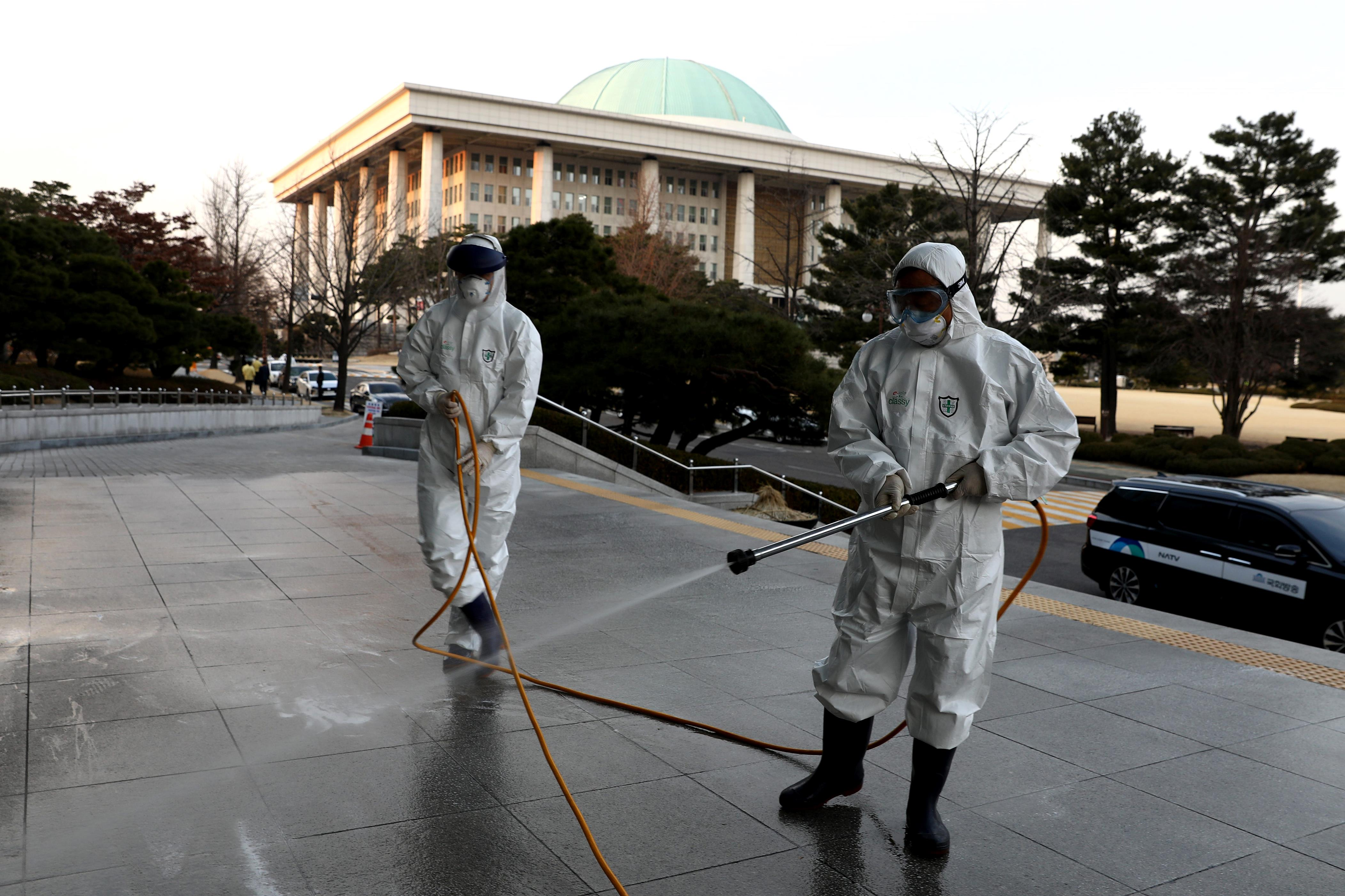 Slide 113 of 113: Disinfection professionals wear protective suits whilst spraying an anti-septic solution against the coronavirus (COVID-19) at a National Assembly on Feb. 24, 2020 in Seoul, South Korea.