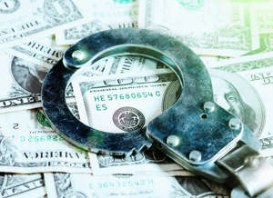 a pair of sunglasses on a table: A pair of handcuffs rests on a US $100 bill among an abundance of dollars, symbolizing fraud, white collar crime, theft, moneylending and many other crimes.