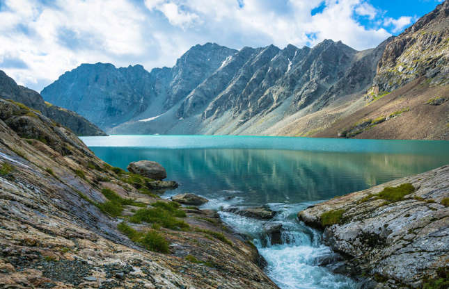 Slide 4 of 59: As far as lakes go, Ala-Kul is one of the world's most impressive. Nestled at an altitude of over 11,483 feet (3,500m)inside the Terskey Alataumountain range in Kyrgyzstan, thisstunning pool isone of the globe's natural gems. Enclosed by snow-capped peaks, theglacial lake covers just 0.5 square miles(1.5sq km)but its vibrant cyan waters are enough to entice and delight even the most jaded of explorer.