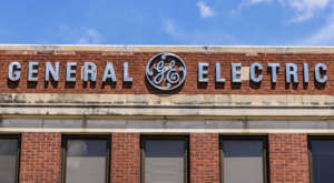 a sign in front of a brick building: General Electric Is Best Left to Hardy Long-Term Investors