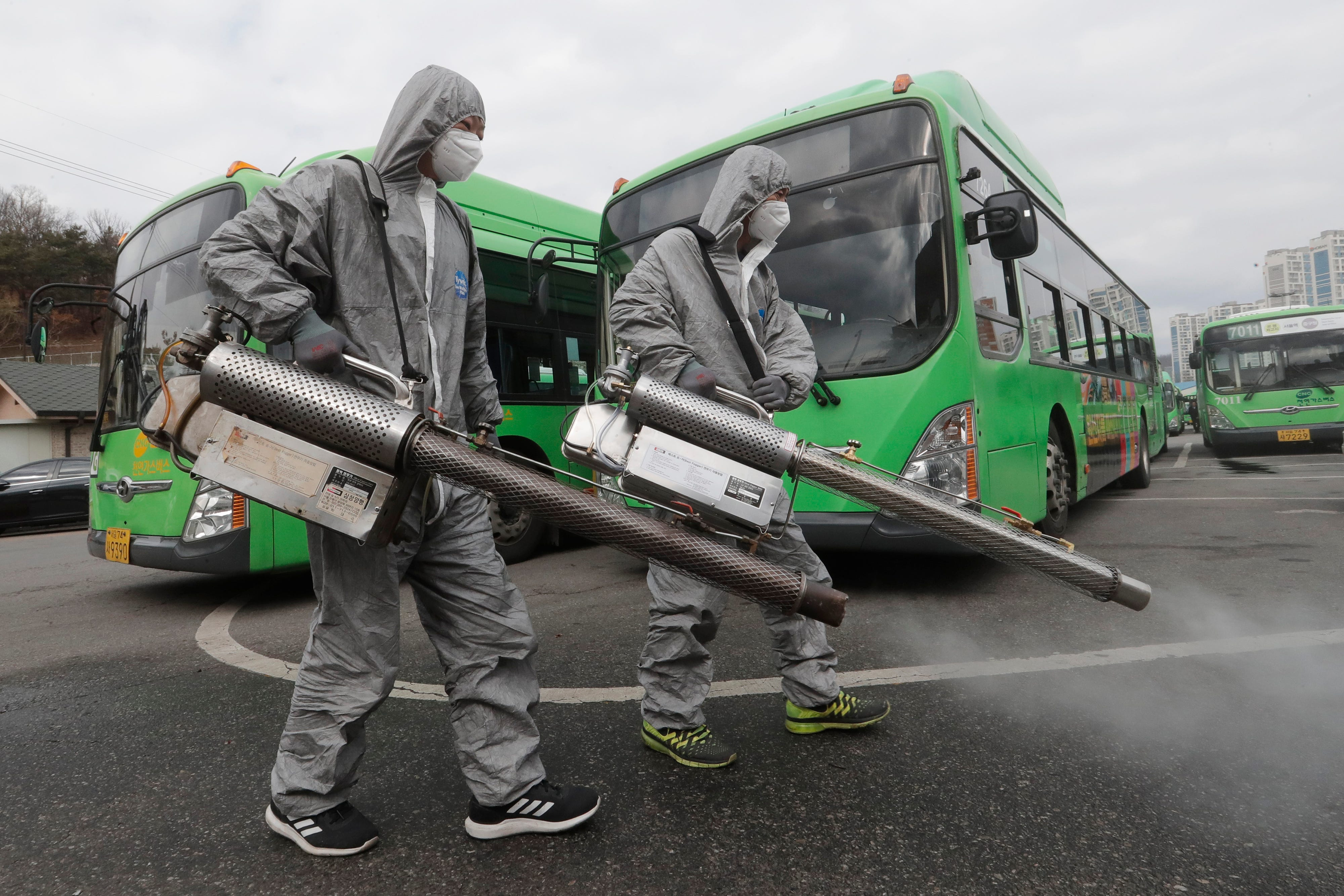 Slide 100 of 113: Workers wearing protective suits spray disinfectant as a precaution against the coronavirus at a bus garage in Seoul, South Korea, Feb. 26, 2020. The number of new virus infections in South Korea jumped again Wednesday and the U.S. military reported its first case among its soldiers based in the Asian country, with his case and many others connected to a southeastern city with an illness cluster.
