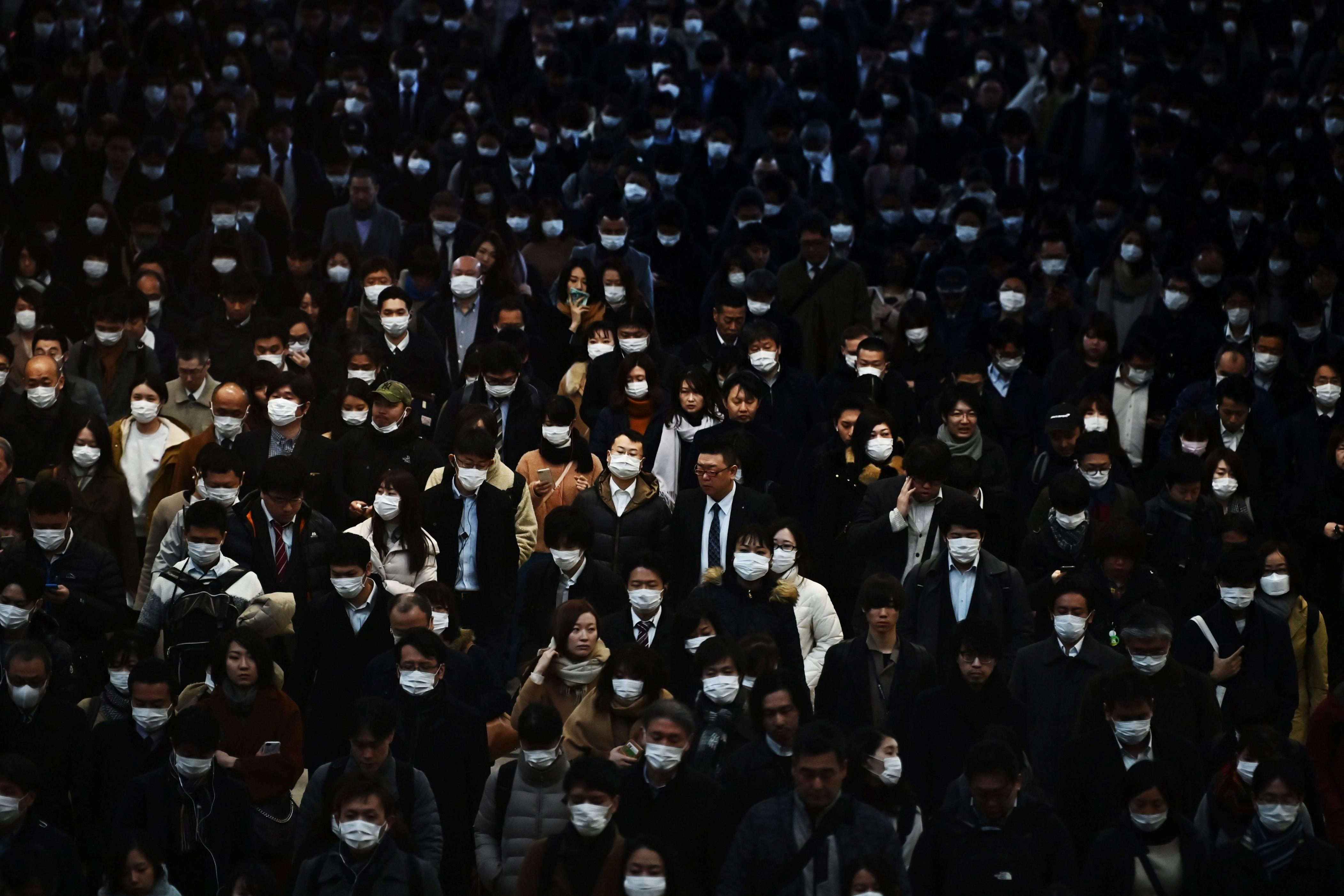 Slide 98 of 113: Mask-clad commuters make their way to work during morning rush hour at the Shinagawa train station in Tokyo on Feb. 28, 2020. Tokyo's key Nikkei index plunged nearly three percent at the open on February 28 after US and European sell-offs with investors worried about the economic impact of the coronavirus outbreak.