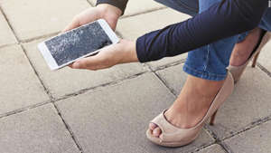 a woman sitting on a sidewalk: Some credit cards will even protect you if your cell phone breaks by paying for it to be repaired or replaced.