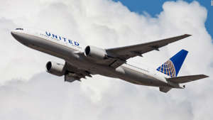 a large passenger jet flying through a cloudy blue sky: Earn points on your travel purchases that can be converted to United miles with the Chase Sapphire Reserve.