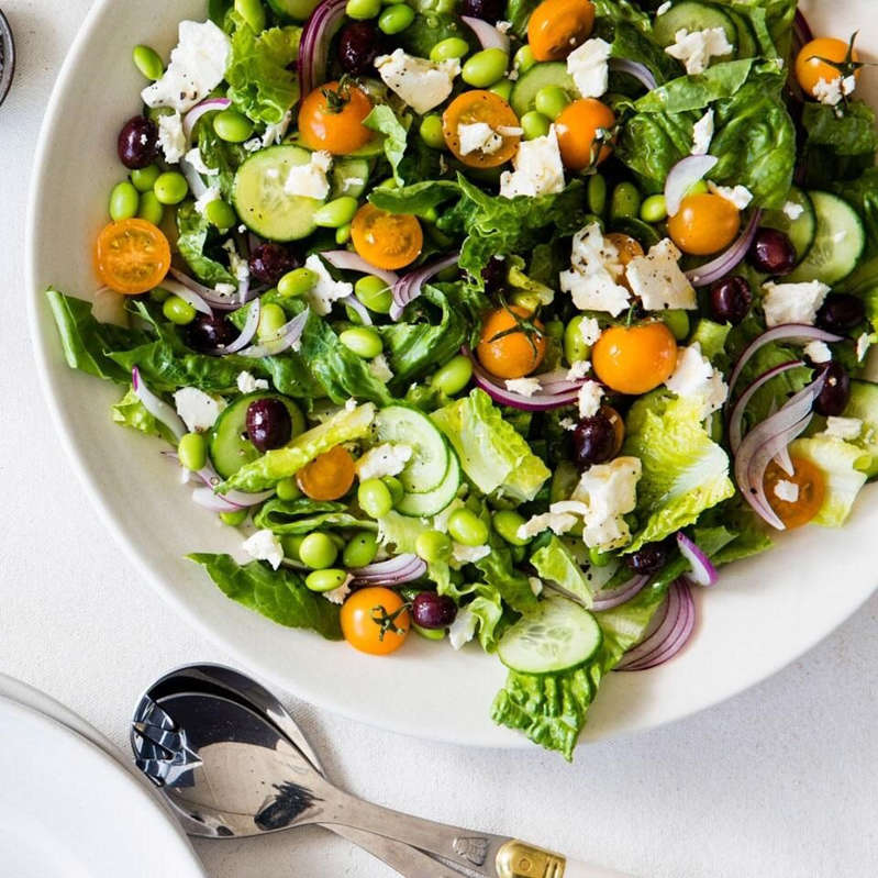 a bowl of salad on a white plate: Greek Salad with Edamame