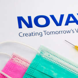 a close up of a piece of paper: Novavax (NVAX) logo surrounded by medical supplies