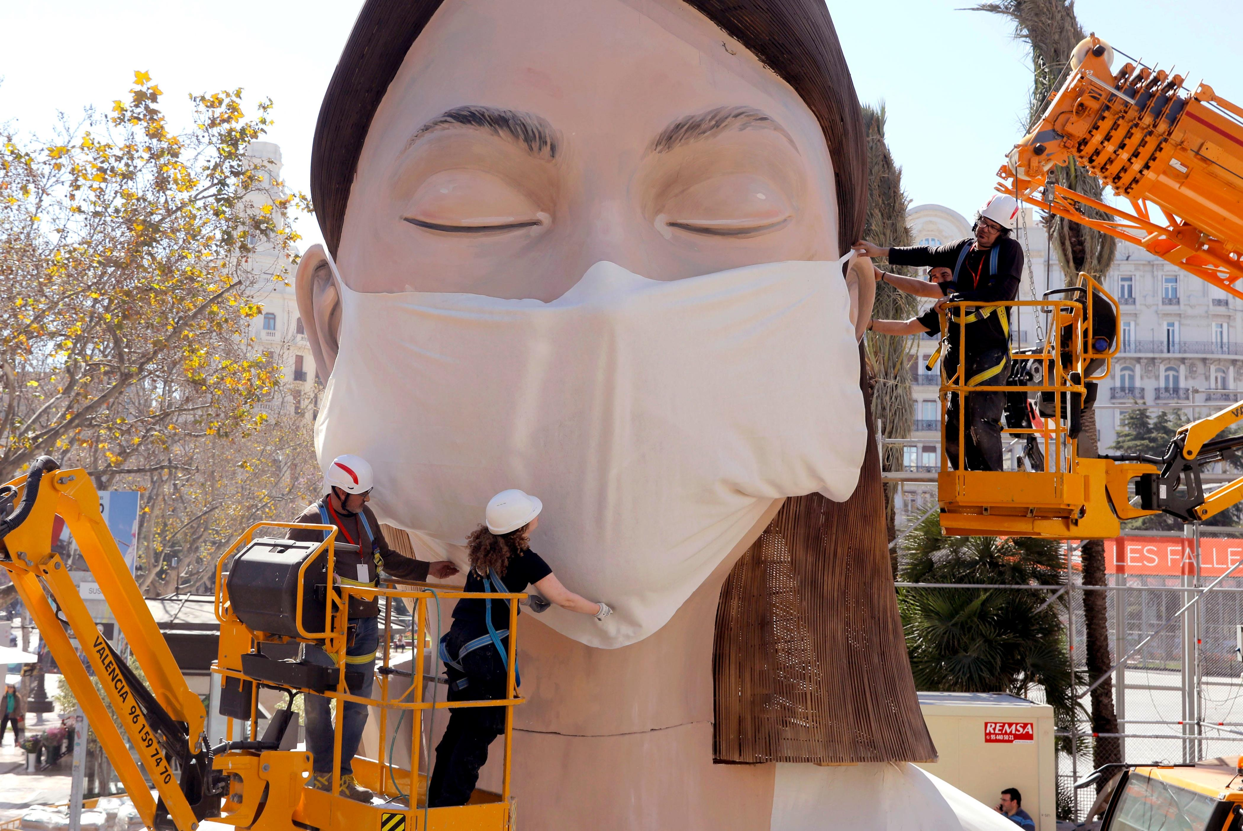 Slide 81 of 113: Workers place a mask on the figure of the Fallas festival in Valencia, Wednesday March 11, 2020. The Fallas festival which was due to take place on March 13 has been cancelled over the coronavirus outbreak. For most people, the new coronavirus causes only mild or moderate symptoms, such as fever and cough. For some, especially older adults and people with existing health problems, it can cause more severe illness, including pneumonia.