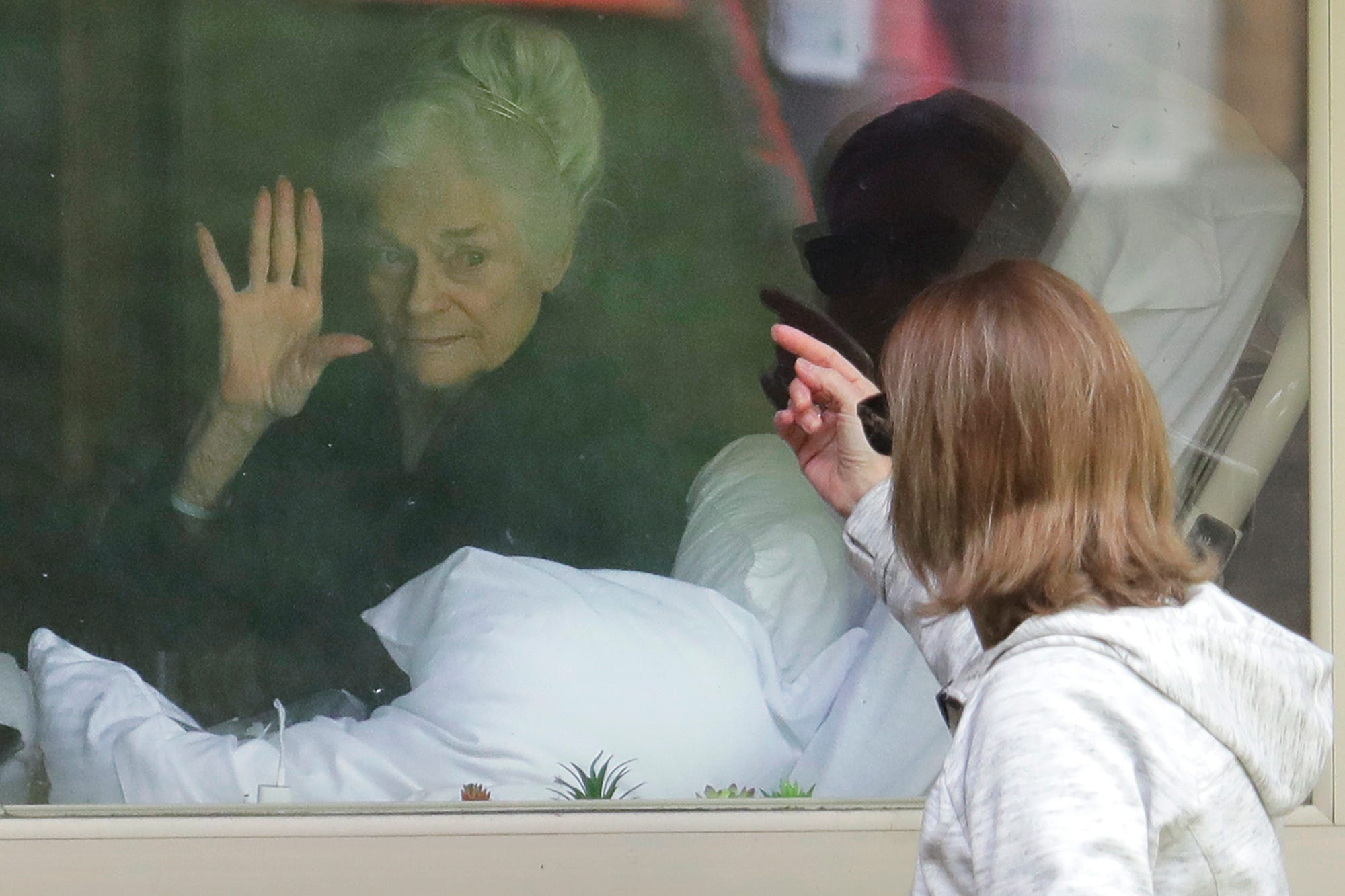 Slide 93 of 105: Judie Shape, left, who has tested positive for the coronavirus, waves to her daughter, Lori Spencer, right, Wednesday, March 11, 2020, as they visit on the phone and look at each other through a window at the Life Care Center in Kirkland, Wash., near Seattle. In-person visits are not allowed at the nursing home. The vast majority of people recover from the new coronavirus. According to the World Health Organization, most people recover in about two to six weeks, depending on the severity of the illness.