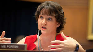 a person sitting at a table: Democrat Katie Porter's confrontation with CDC director goes viral