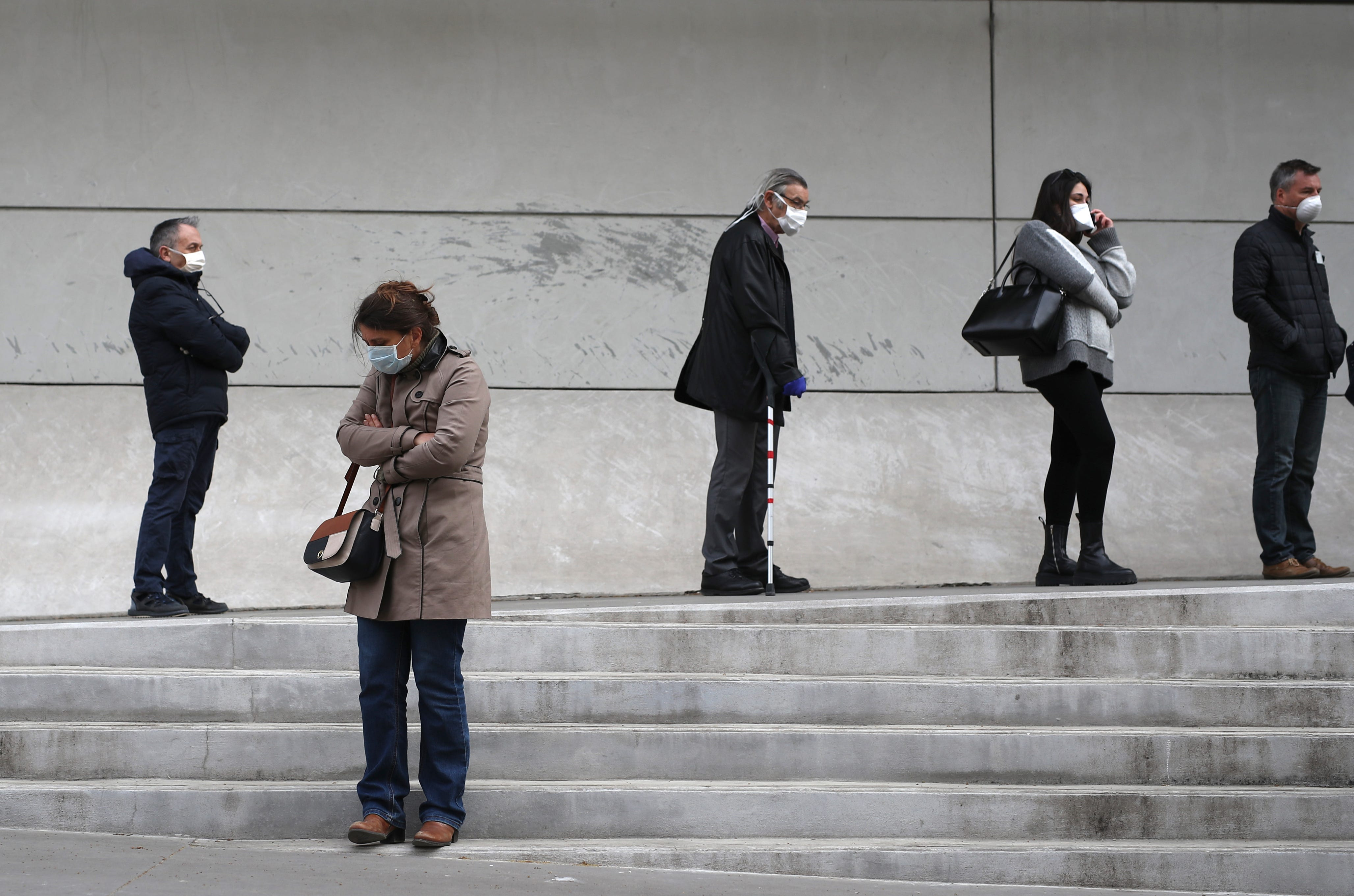 Slide 15 of 113: People wait in line to get a coronavirus test outside the La Timone hospital in Marseille, France, March 23, 2020.