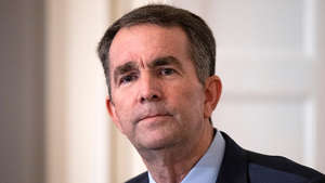 Ralph Northam wearing a suit and tie smiling and looking at the camera: Northam backs primary challenger in Virginia attorney general's race