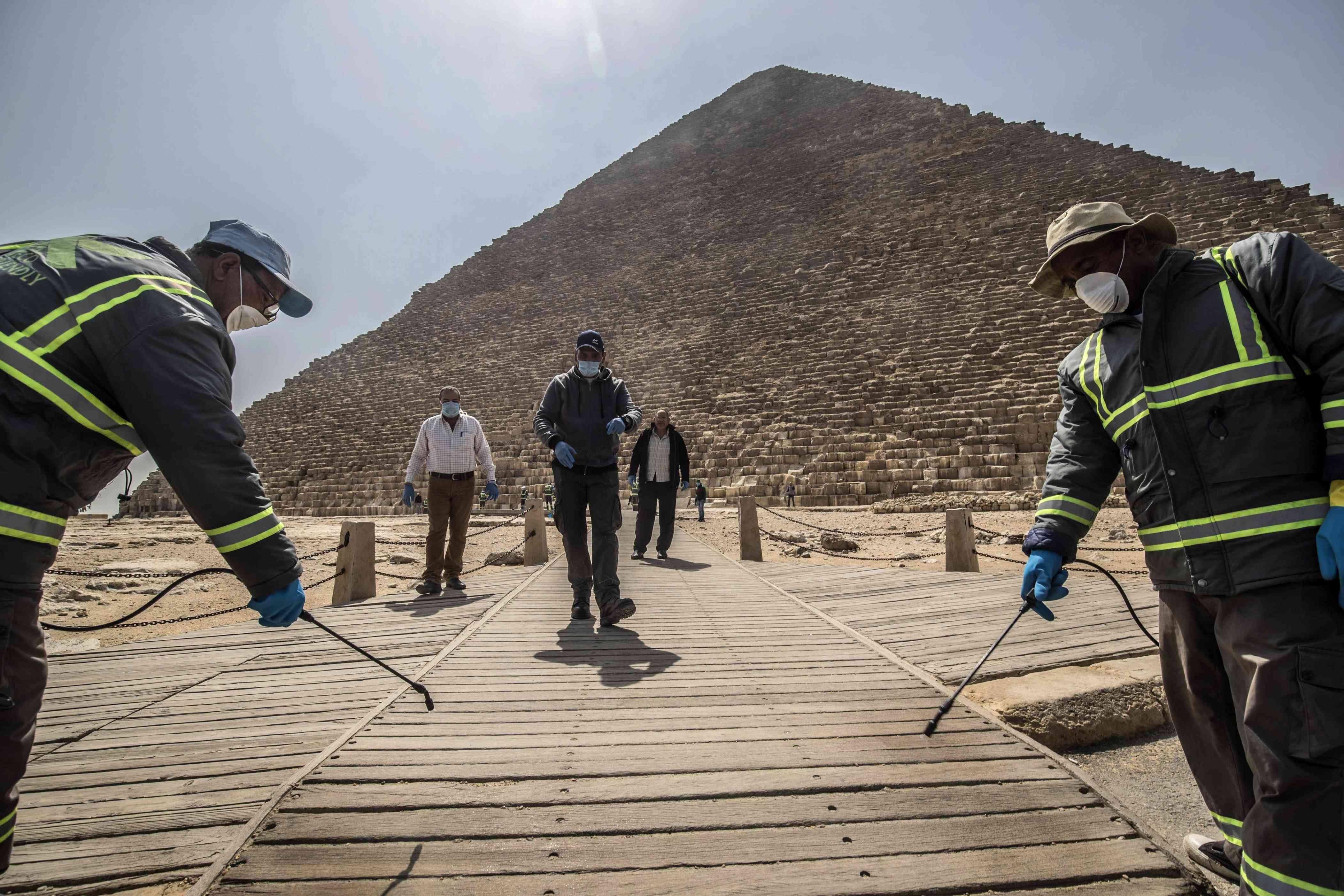 Slide 3 of 40: Egyptian municipality workers disinfect the Giza pyramids necropolis on the southwestern outskirts of the Egyptian capital Cairo on March 25, 2020 as protective a measure against the spread of the coronavirus COVID-19.