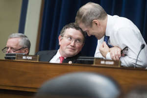 Rep. Thomas Massie, R-Ky., center, speaks with Congressman Jim Jordan, R-Ohio, during a House Oversight and Reform Committee hearing on April 9, 2019.