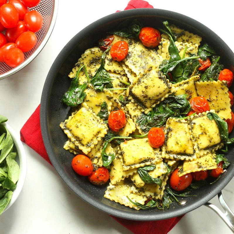 a bowl of salad: pan of Pesto Ravioli with Spinach and Tomatoes