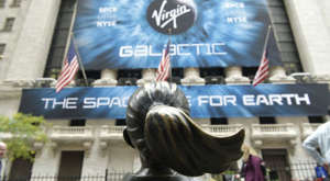 a person standing in front of a building: Virgin Galactic (SPCE) billboard on the New York Stock Exchange, across from the Fearless Girl statue. aerospace stocks