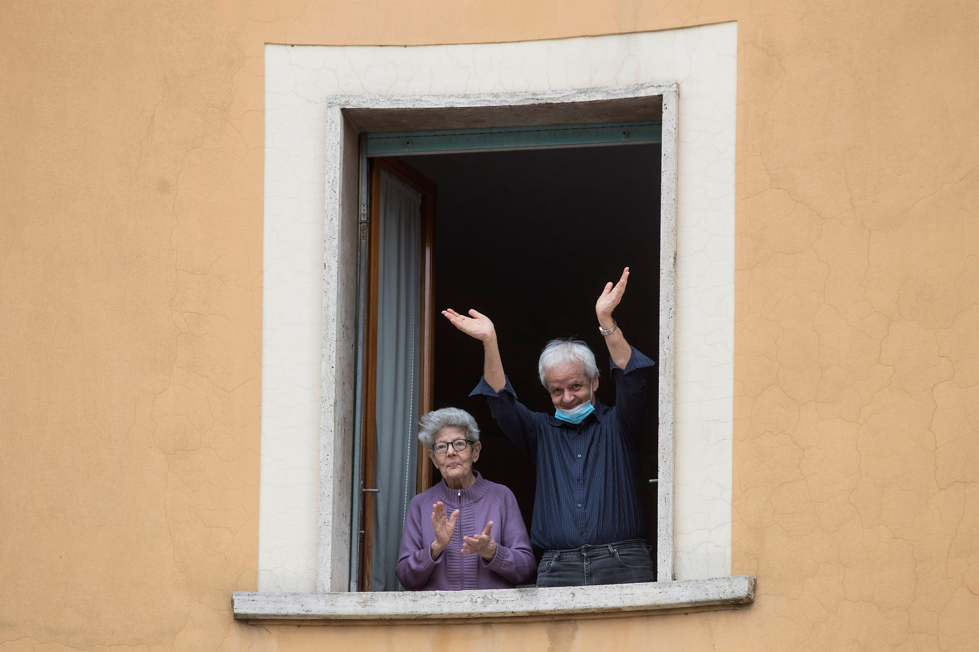 Slide 77 of 113: People clap their hands and wave, in Rome, Saturday, March 14, 2020. At noon in Italy, people came out on their balconies, terraces, gardens or simply leaned out from open windows to clap for several minute in a gesture of thanks for the doctors, nurses, other hospital staff and ambulance crews who have been treating and helping infected patients.
