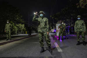 QUEZON, PHILIPPINES - MARCH 15: Police officers and troops are seen wearing facemasks as they stand guard at a checkpoint as authorities begin implementing a lockdown on Manila on March 15, 2020 in the outskirts of Metro Manila, Philippines. The Philippine government is placing some 12 million people in the capital Manila on lockdown as well as suspending government work for a month to prevent the spread of COVID-19. As of Saturday evening, the Philippines' Department of Health has confirmed 111 cases of the deadly coronavirus in the country, with at least 8 recorded fatalities. (Photo by Ezra Acayan/Getty Images)
