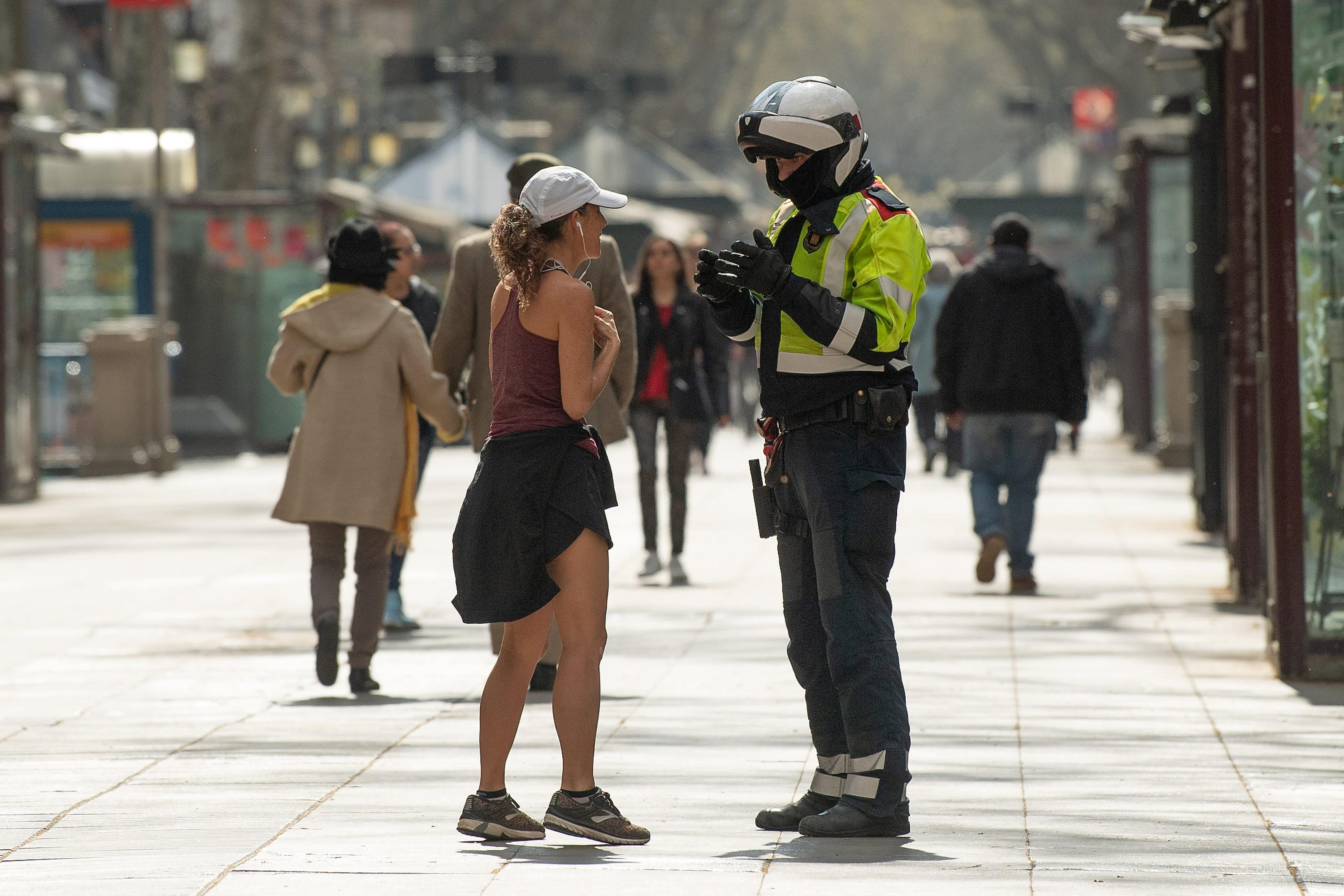 Slide 76 of 113: A Catalan Autonomous police officer, Mosso d'Esquadra, halts a woman who was jogging through Las Ramblas on March 15, 2020 in Barcelona, Spain. As part of the measures against the virus expansion the Government has declared a 15-day state of emergency which will come into effect today.