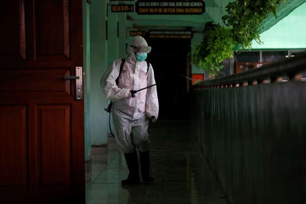 الشريحة 1 من 72: A volunteer from Indonesia's Red Cross sprays disinfectant at the corridor of a school closed amid the spread of coronavirus (COVID-19) in Jakarta, Indonesia, March 16, 2020. REUTERS/Willy Kurniawan