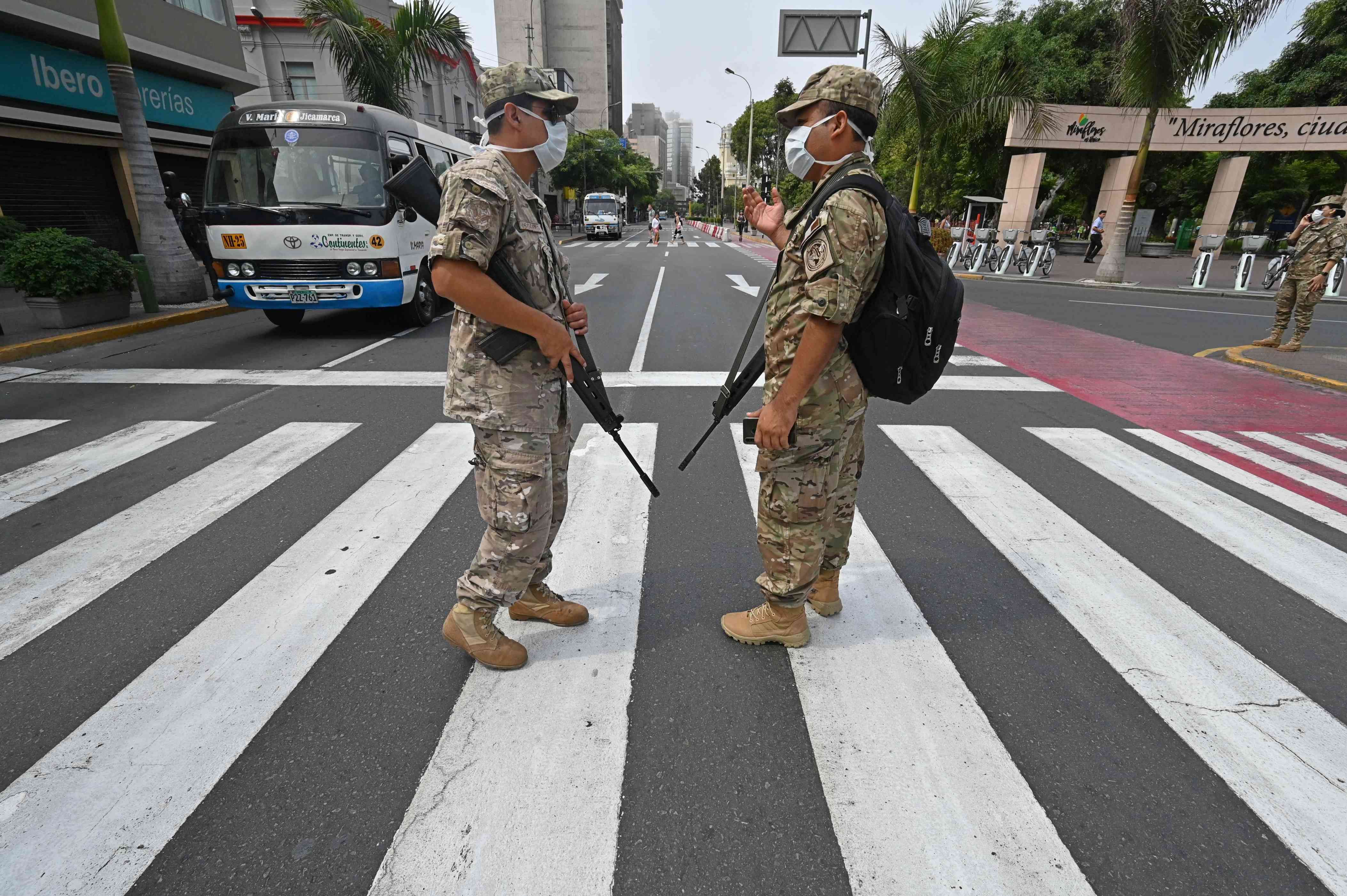Slide 66 of 113: Peruvian army soldiers control traffic in Lima on March 16, 2020, in an attempt to persuade the population to stay at home, one day after President Martin Vizcarra announced a State of Emergency and a two-week nationwide home-stay quarantine together with the closure of all borders to fight the spread of the novel COVID-19 coronavirus. No fatalities have been recorded of the 86 cases of Covid-19 detected in the country.