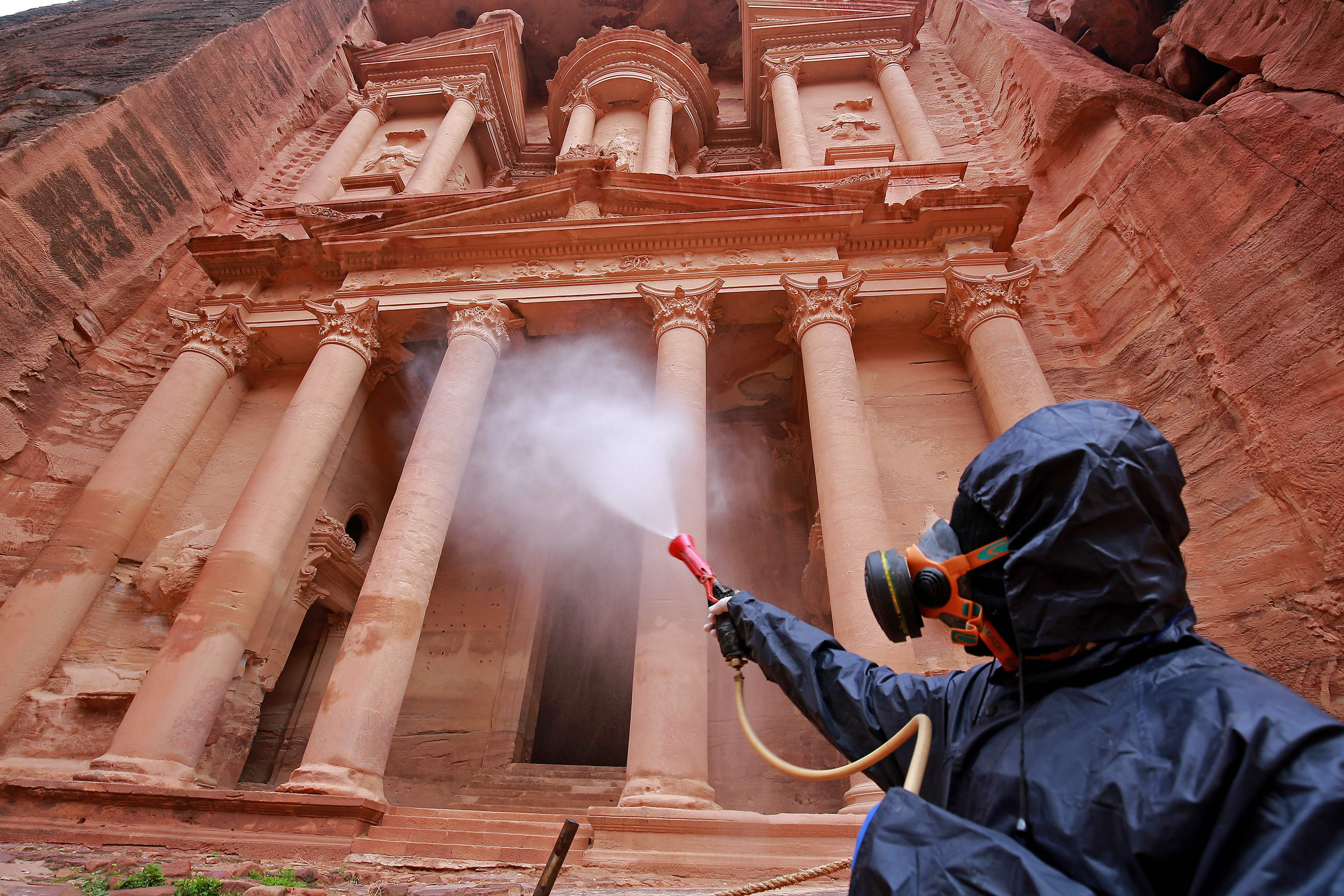 Slide 60 of 113: A worker sprays disinfectant in Jordan's archaeological city of Petra south of the capital Amman on March 17, 2020, to prevent the spread of COVID-19.