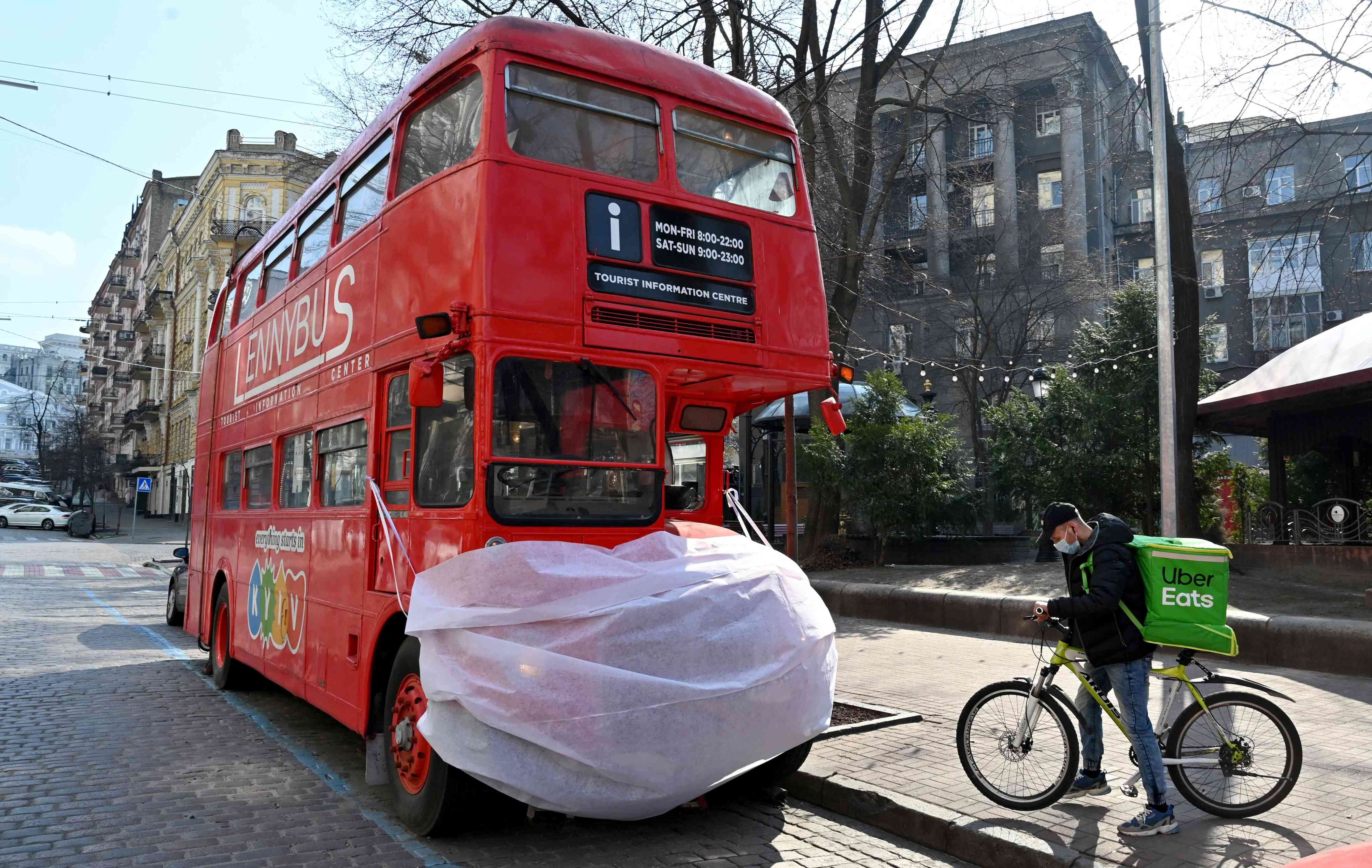 "Slide 54 of 113: A deliveryman wearing a protective face mask pauses by a double-deck tourist bus decorated with a huge mask in the center of the Ukrainian capital of Kiev on March 18, 2020. Ukraine late on March 16 announced shutdowns of public transport, bars, restaurants and shopping malls to stem the spread of the coronavirus after President Volodymyr Zelensky promised to act ""harshly, urgently, perhaps unpopularly"". The government supported Zelensky's proposals and introduced restrictions on domestic movement, including full closure of the country's three metro systems in Kiev, Kharkiv and Dniprom until April 3."