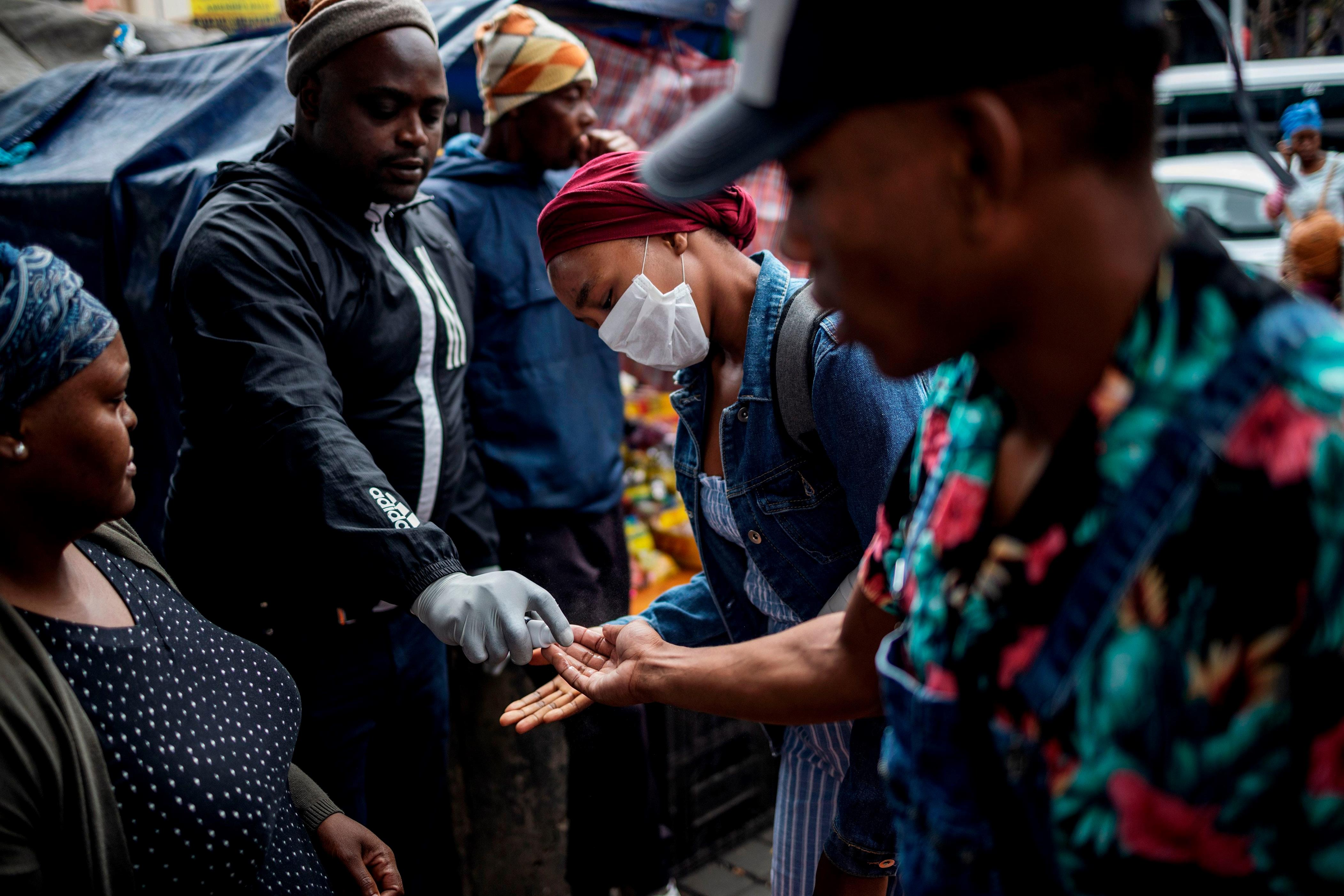 Slide 57 of 113: A man sprays commuters with hand sanitizer as a preventive measures in Johannesburg, South Africa on March 18, 2020. African countries have been among the last to be hit by the global COVID-19 coronavirus epidemic but as cases rise, many nations are now taking strict measures to block the deadly illness.