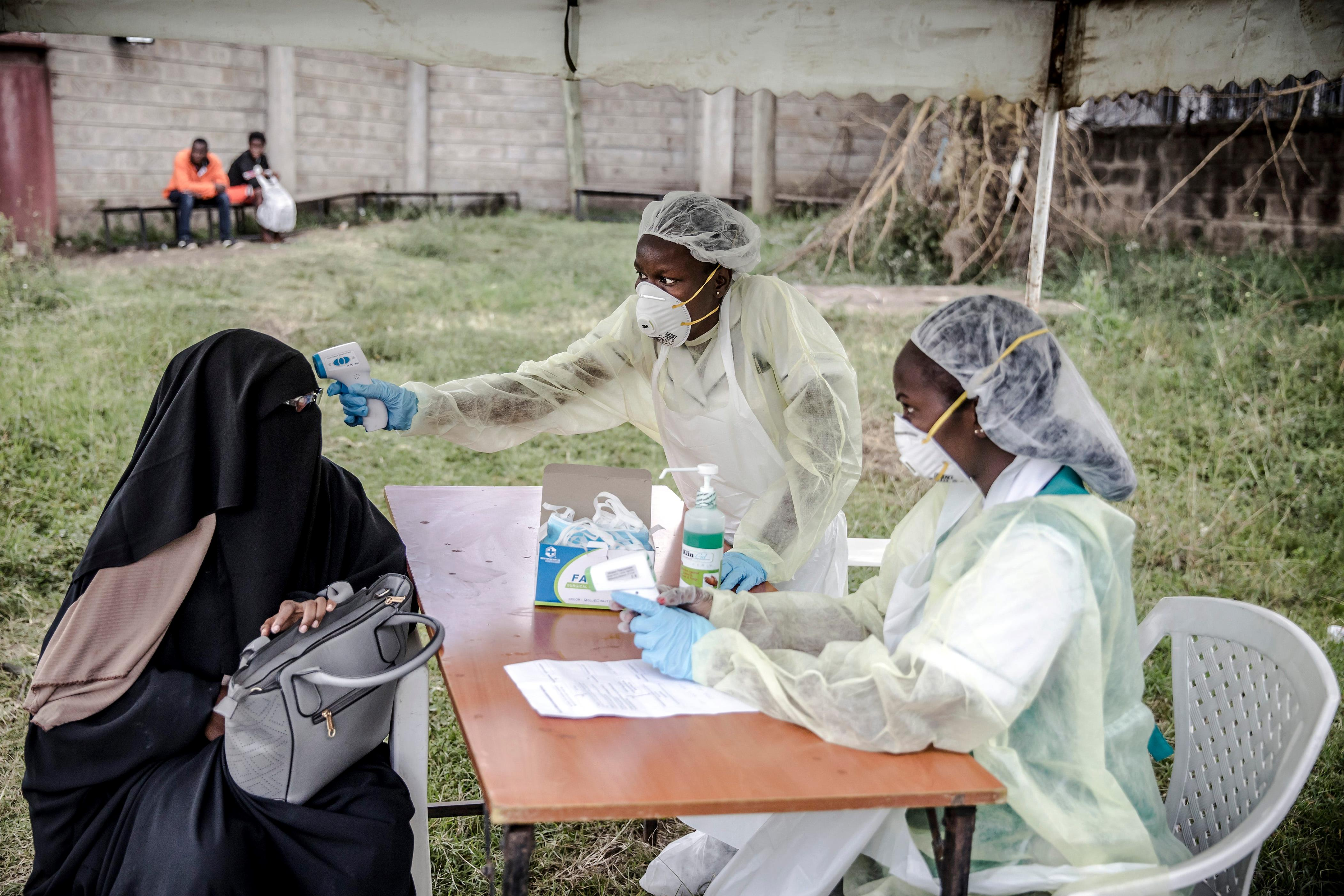 Slide 46 of 113: Health personnel measure the temperature of a visitor at the entrance of the Mbagathi Hospital in Nairobi, Kenya on March 18, 2020. The Government of Kenya confirmed new positive cases of COVID-19 coronavirus on March 18, 2020, bringing the total official number of cases in the East African country to 7. African countries have been among the last to be hit by the global COVID-19 coronavirus epidemic but as cases rise, many nations are now taking strict measures to block the deadly illness.