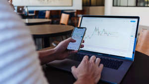 a person using a laptop computer sitting on top of a desk: Although stock prices rise and fall all the time, in general, the stock market follows an upward trajectory. If you are saving for the long term, investing in stock can be a great way to grow your wealth.