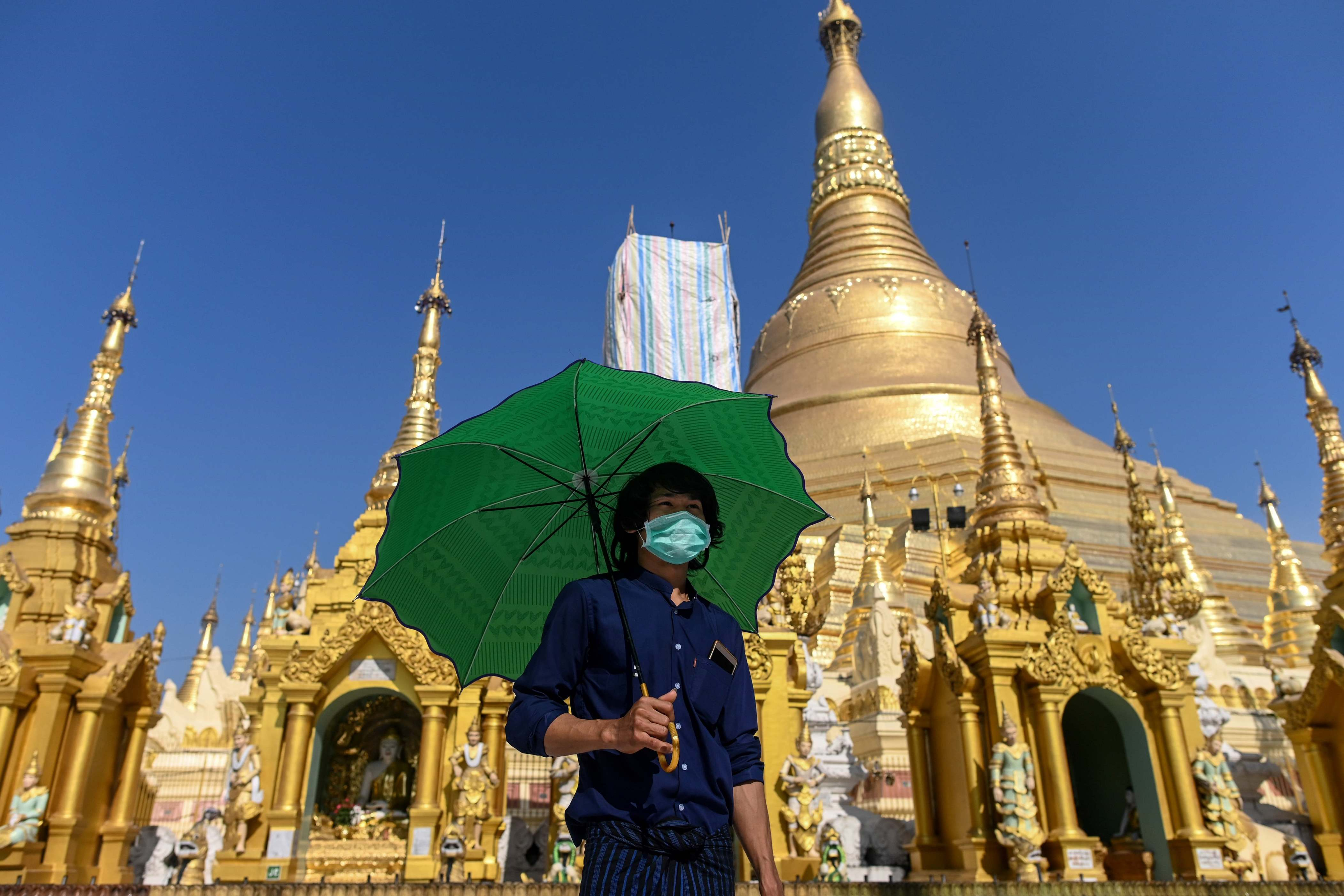 Slide 48 of 113: A man wears a face mask, amid concerns of the spread of the COVID-19 coronavirus, as he visits Shwedagon Pagoda in Yangon on March 18, 2020.