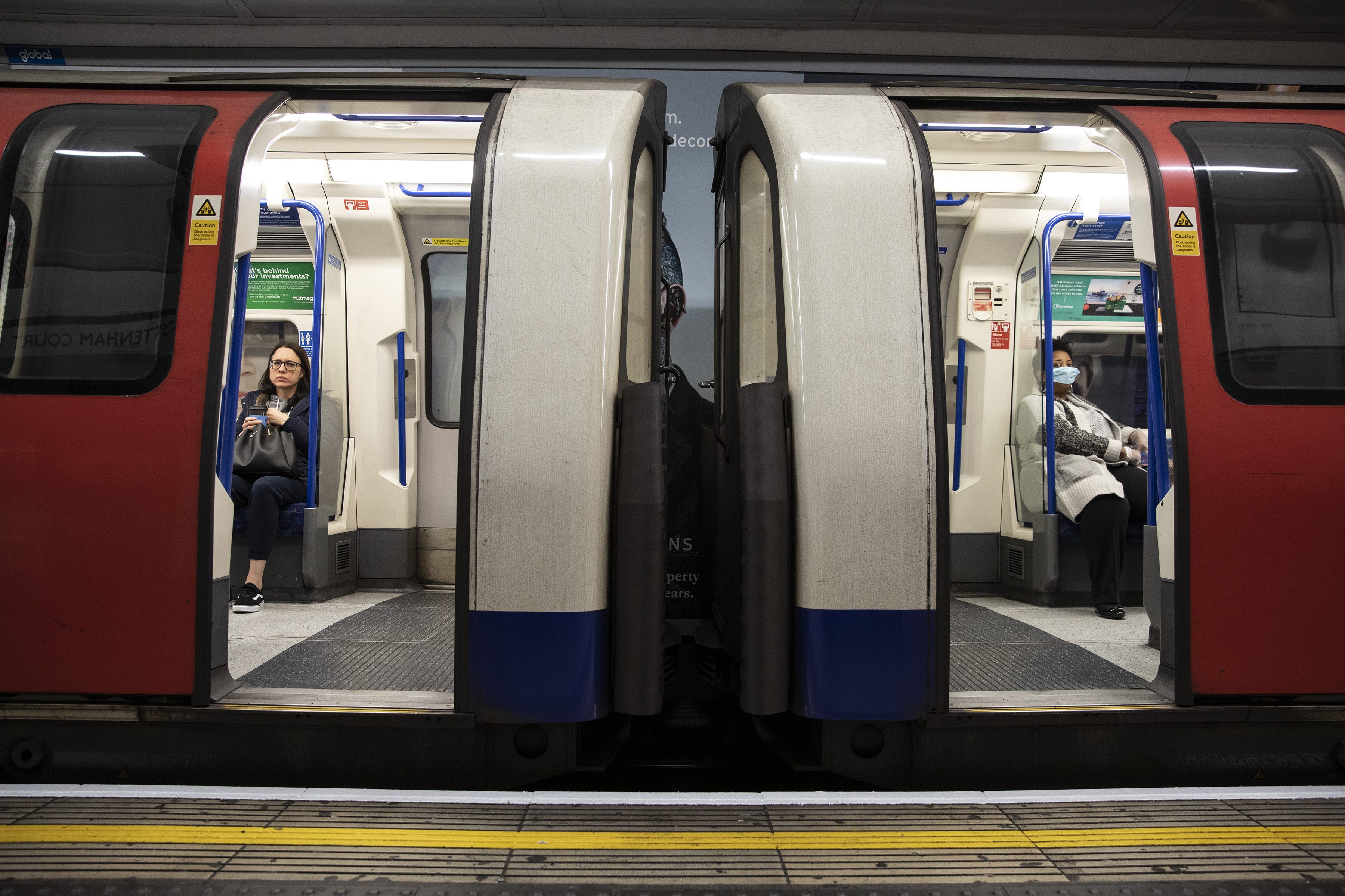 Slide 40 of 113: Passengers ride the tube on March 19, 2020 in London, England. Transport for London announced the closure of up to 40 stations as officials advised against non-essential travel. Bus and London Overground service will also be reduced.
