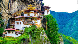 a house with Paro Taktsang in the background: The prime minister of tiny Bhutan is credited with launching World Happiness Day.