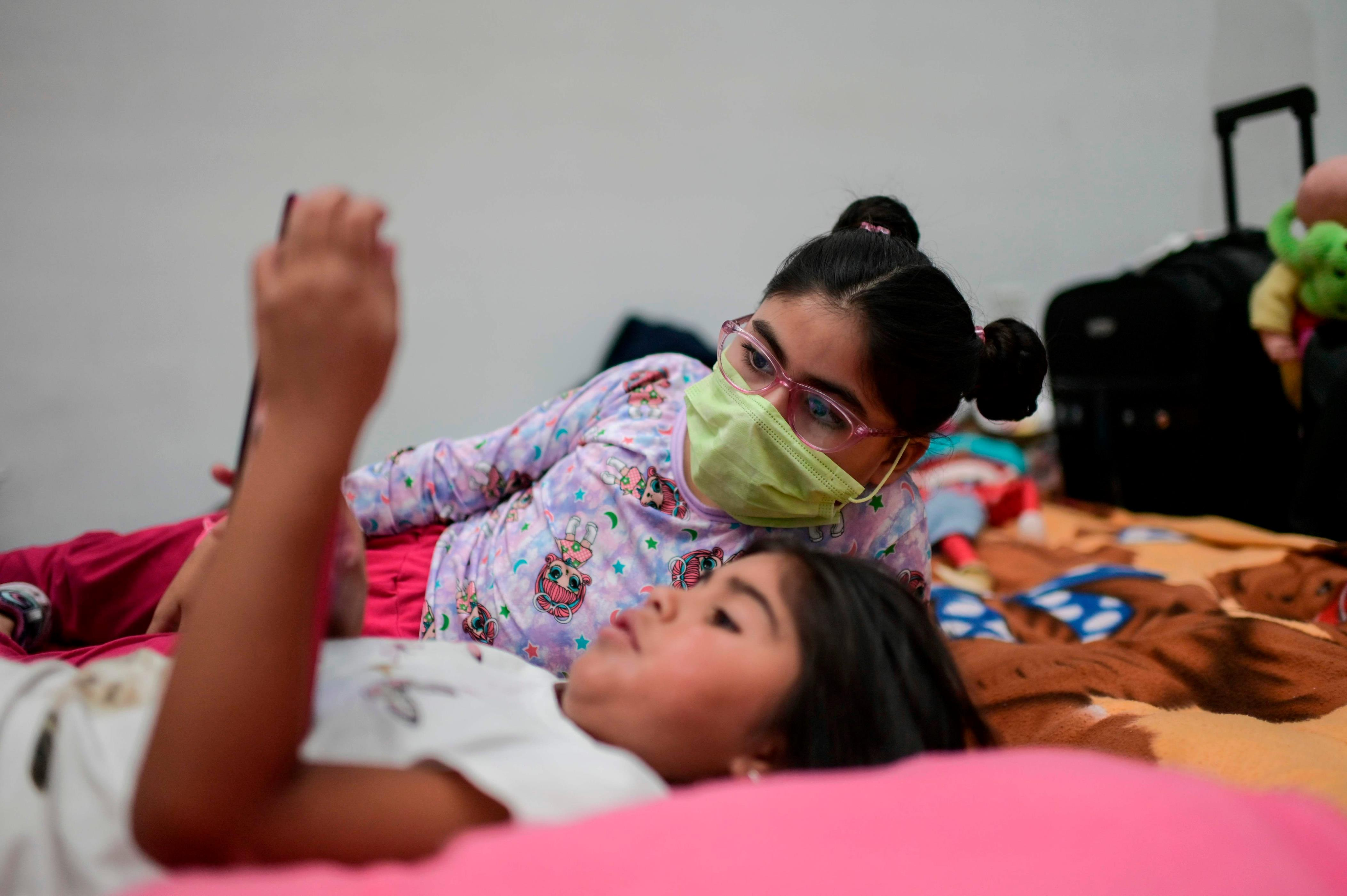 Slide 28 of 113: Chilean passengers rest as they remain standed at Mexico City's international airport, on March 21, 2020.