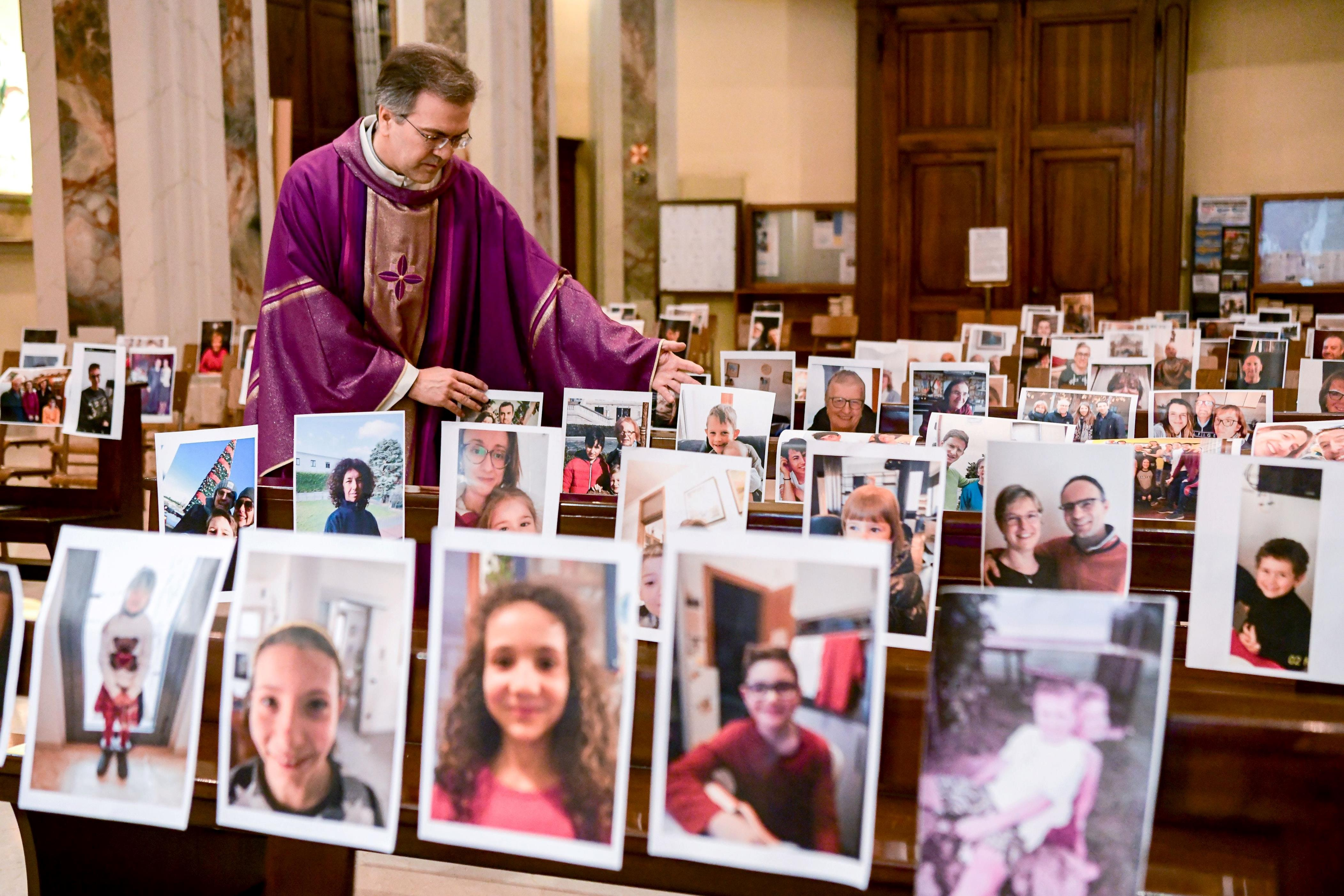 "Slide 18 of 113: Don Giuseppe Corbari, parson of the Church of Robbiano, adjusts prints of selfies sent by his congregation and glued to empty pews before celebrating Sunday mass in Giussano on March 22, 2020. Italian Prime Minister Giuseppe Conte on March 21, 2020, ordered all non-essential companies and factories to close nationwide to stem a coronavirus pandemic that has killed 4,825 people in the country in a month. ""The decision taken by the government is to close down all productive activity throughout the territory that is not strictly necessary, crucial, indispensable, to guarantee us essential goods and services,"" Conte said in a late-night TV address."