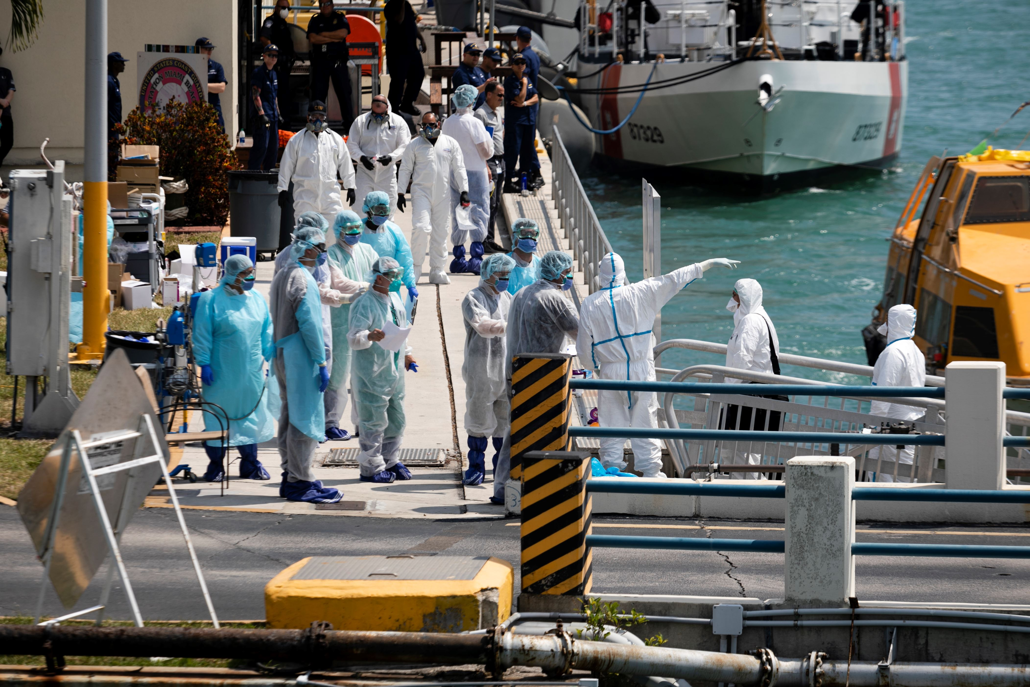 Medical staff receive suspected Coronovirus patients as they arrive at U.S. Coast Guard Base Miami Beach on March 26, 2020 in Miami, Florida. According to reports, two Costa Cruises ships, the Favolosa and the Magica, are anchored off the coast of Miami with approximately 30 people experiencing flu-like symptoms of COVID-19.