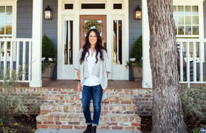 a person standing in front of a brick building: Described as one of the most ambitious Fixer Upper projects to date, this 115-year-old Craftsman home was dilapidated and rundown. With a little help from Chip and Joanna Gaines, the old house was renovated and turned into a stunning house fit for modern living. You're not going to believe the transformation. Click or scroll for more...