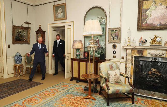 Slide 31 of 53: Prince Charles and Camilla regularly welcome guests from around the world to their London home. Before the Prince moved into the abode, it underwent extensive redecoration and redesign with new color schemes and fabric introduced to the furniture. Most meetings take place in the formal living room which has blue-toned furniture, fringed lamps and historic artwork. Here, Prince Charles can be seen introducing King Willem-Alexander, ruler of the Netherlands, to the formal living room in October 2018.