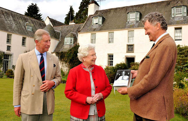 Slide 29 of 53: Here, Queen Elizabeth II and Prince Charles are being presented with a first edition of Queen Elizabeth the Queen Mother: The Official Biographyby the author William Shawcross in the garden of Birkhall.The late Queen Mother loved Birkhall and when visiting she would indulgein her love ofsalmon fishing, often while wearing tartan and tweed. Over the years, the famously green-thumbed Prince Charles has made a passion project ofrestoring the beautiful gardens to their formerglory after they were devastated by flooding in 2016.