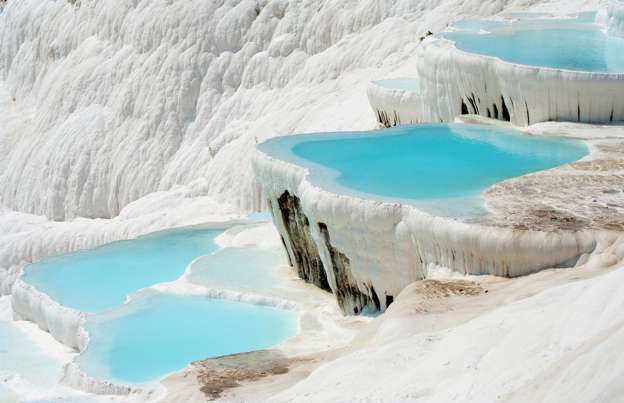 Slide 22 of 30: Bright white and shimmering turquoise are a match made in hue heaven, and there are few places that demonstrate that more gorgeously than the thermal pools of Pamukkale, a town in western Turkey. The travertine terraces, whose staggered steps tumble down the mountainside, are the result of limestone deposited over millennia from the natural hot springs, which flow over and form milky-blue pools.