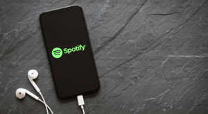 a close up of a cell phone: Spotify (SPOT) logo is on the screen of a smartphone with headphones plugged in.