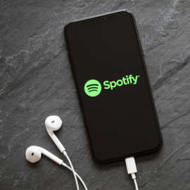 Spotify (SPOT) logo is on the screen of a smartphone with headphones plugged in.