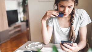 a woman sitting at a table using a cell phone: If you've decided to make paying off debt your priority, you might be tempted to funnel all your income toward necessary expenses and debt repayment and put a pause on contributions to your retirement savings and emergency savings.