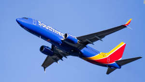a large passenger jet flying through a blue sky: Use the Southwest Premier card to help earn the Southwest Companion Pass.