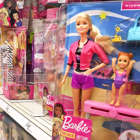 a person standing in front of a store: Barbie dolls for sale at a Target store.