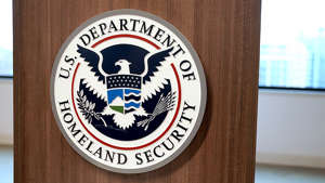 a sign on a wooden surface: Second senior official leaving DHS in a week