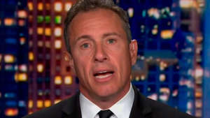 Chris Cuomo wearing a suit and tie smiling at the camera