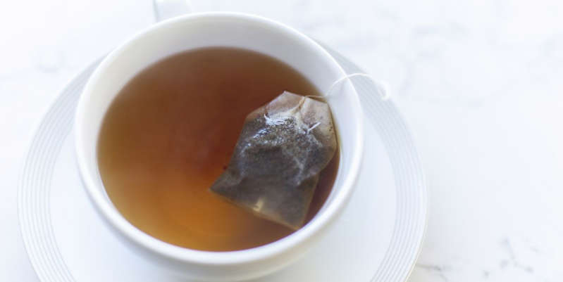 a close up of a coffee cup on a plate: Here's how Sleepytime tea actually works, according to experts.