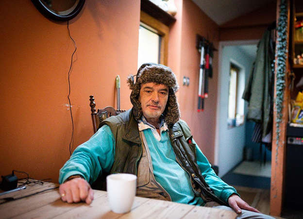 Ian Bailey sitting at a table using a laptop: Ian Bailey says he can't return to his home in the UK because a European Arrest Warrant would be activated if he did Pic Tom Honan.