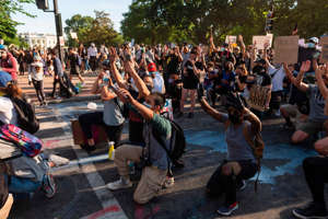 a group of people standing in front of a crowd: Protesters take a knee and raise their hands facing riot police near the White House on June 1, 2020 as demonstrations against George Floyd's death continue. Roberto Schmidt/AFP via Getty Images